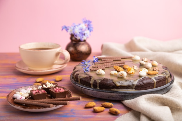 Домашний шоколадный торт-брауни с карамельным кремом и миндалем с чашкой кофе на цветной и розовой поверхности и льняной ткани