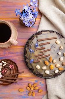 キャラメルクリームとアーモンドと自家製チョコレートブラウニーケーキと色付きの木製の背景にコーヒーのカップ。トップビュー、クローズアップ。