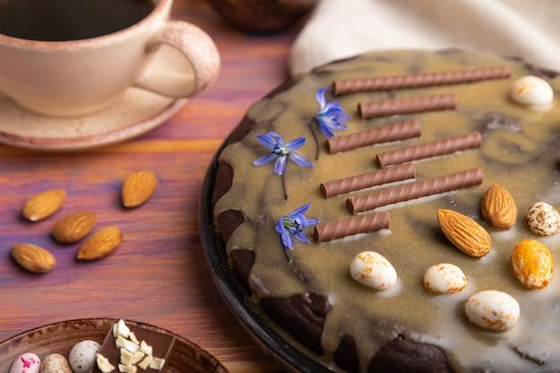 キャラメルクリームとアーモンドと自家製チョコレートブラウニーケーキと色付きの木製の背景にコーヒーのカップ。