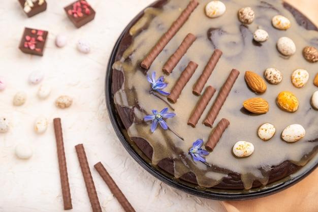 Домашний шоколадный торт с карамельным кремом и миндалем с чашкой кофе на белой бетонной поверхности и оранжевой ткани