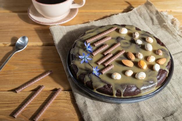 木製の背景にコーヒーのカップとキャラメルクリームとアーモンドの自家製チョコレートブラウニーケーキ。サイドビュー、ハードライト。