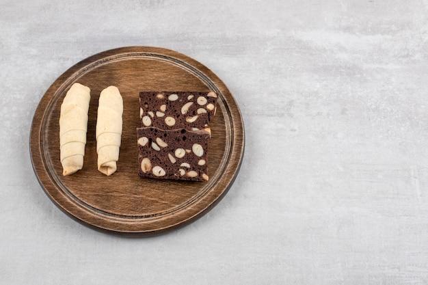 Домашние шоколадные пирожные и рулетики на доске, на мраморном столе