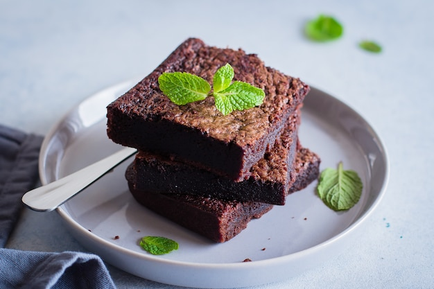 Homemade chocolate brownies on blue stone background