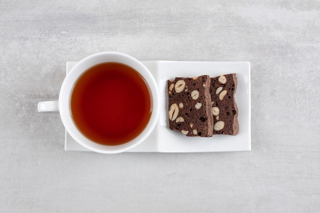 Homemade chocolate brownies and a cup of tea on a dish , on the marble table.