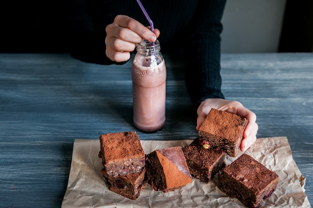Homemade chocolate brownies on dark surface. and bottles with hot chocolate