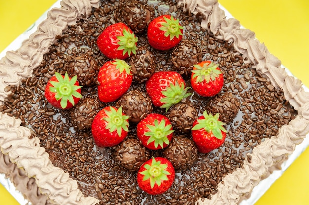 Homemade chocolate cake covered with chocolate and strawberries known in brazil as brigadeiro cake
