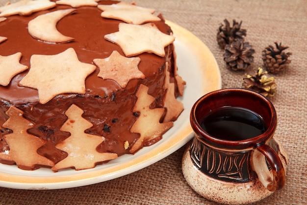 クリスマスの飾りと一杯のコーヒー、荒布の上にコーンで飾られた自家製チョコレートケーキ。