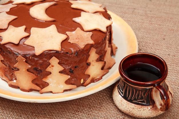 クリスマスの飾りと荒布にコーヒーのカップで飾られた自家製チョコレートケーキ。