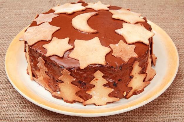 背景に荒布を着た皿にクリスマスの飾りで飾られた自家製チョコレートケーキ。