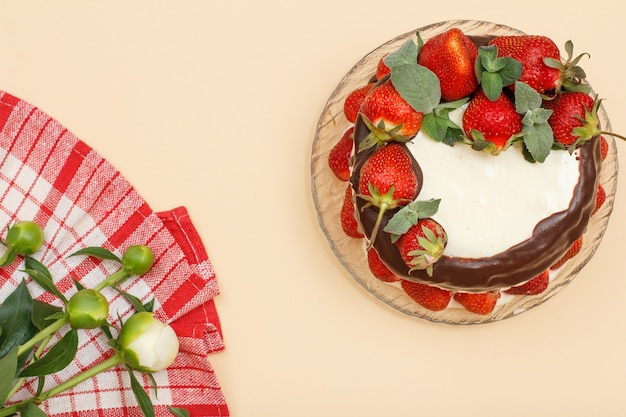 Homemade chocolate cake decorated with fresh strawberries and leaves of mint on glass plate and kitchen napkin with bouquet of peonies on beige color background. top view