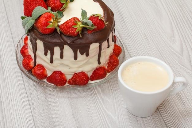 ガラス板に新鮮なイチゴと灰色の木製の背景にコーヒーのカップで飾られた自家製チョコレートケーキ