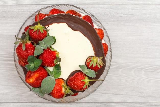 ガラス板と灰色の木製の背景に新鮮なイチゴで飾られた自家製チョコレートケーキ。コピースペースのある上面図