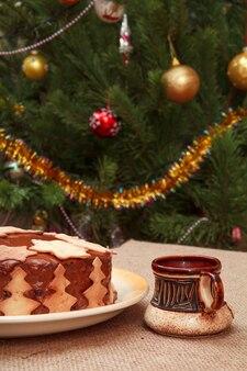 クリスマスツリーを背景にテーブルに飾りとコーヒーのカップで飾られた自家製チョコレートケーキ。