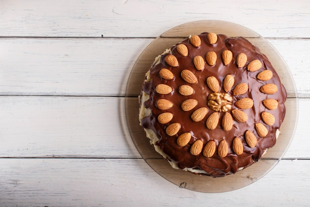 Homemade chocolate cake with almonds on white wooden background.