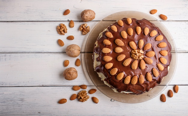 Homemade chocolate cake with almonds on white wooden table.