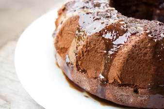 Homemade chocolate cake with chocolate syrup topping on white plate. Ring cake.