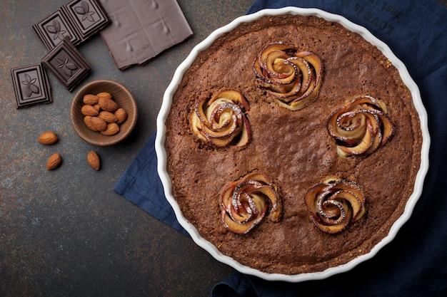 木の暗いコンクリートまたは石の背景にフランジパーヌとリンゴの花と自家製チョコレートケーキ。セレクティブフォーカス。上面図。スペースをコピーします。