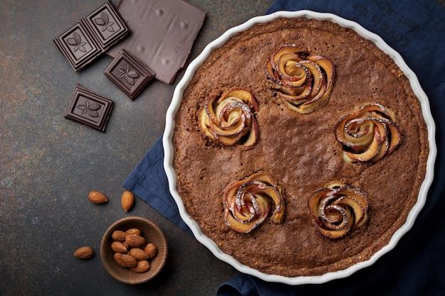 木の表面の暗いコンクリートまたは石の表面にフランジパーヌとリンゴの花が付いた自家製チョコレートケーキ。セレクティブフォーカス。上面図。