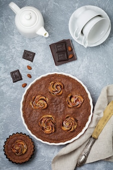 ライトグレーのコンクリート表面にフランジパーヌとリンゴの花が付いた自家製チョコレートケーキ
