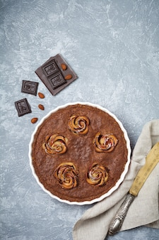 Homemade chocolate cake with frangipane and apple blossoms on light gray concrete surface