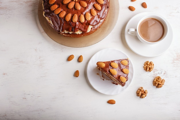 Homemade chocolate cake with milk cream, caramel and almonds on whitewoodcup of coffee.