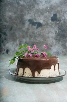 暗い素朴な机の上に花で飾られたピーナッツバタークリームの層を持つ自家製チョコレートケーキ。側面図。