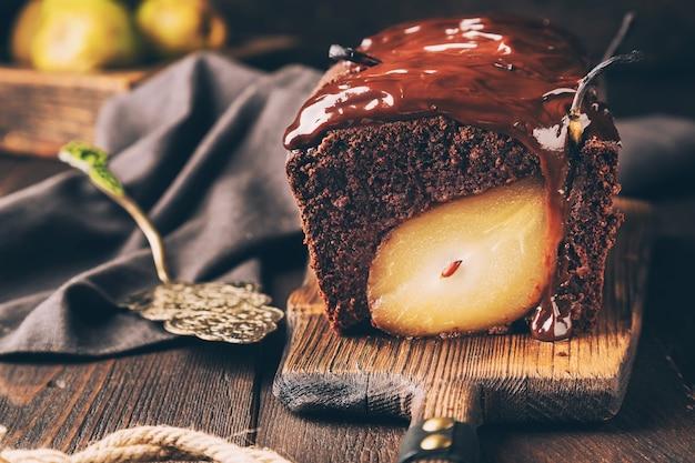 소박한 나무 배경에 배와 홈메이드 초콜릿 케이크. 퍼지와 브라우니. 선택적 초점입니다.