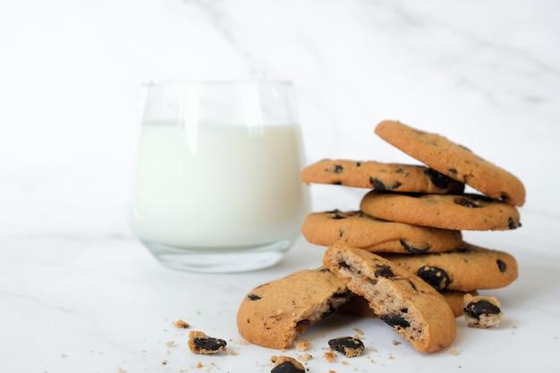 大理石の背景に自家製チョコレートチップクッキーとミルクのガラス