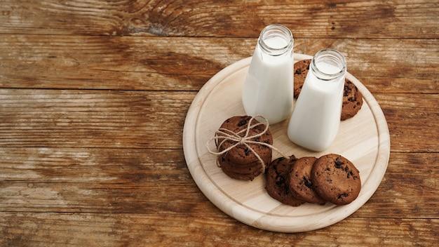 素朴なスタイルの木製の背景に自家製チョコレートチップクッキーとミルク。甘いおやつ。テキストの場所