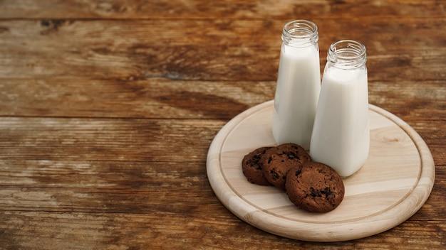 素朴なスタイルの木製の背景に自家製チョコレートチップクッキーとミルク。甘いおやつ