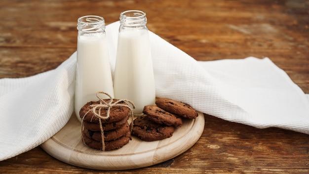 素朴なスタイルの木製の表面に自家製チョコレートチップクッキーとミルク。甘いおやつ