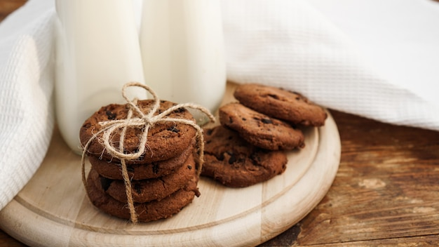 Homemade chocolate chip cookies and milk on wooden background in rustic style. sweet snack