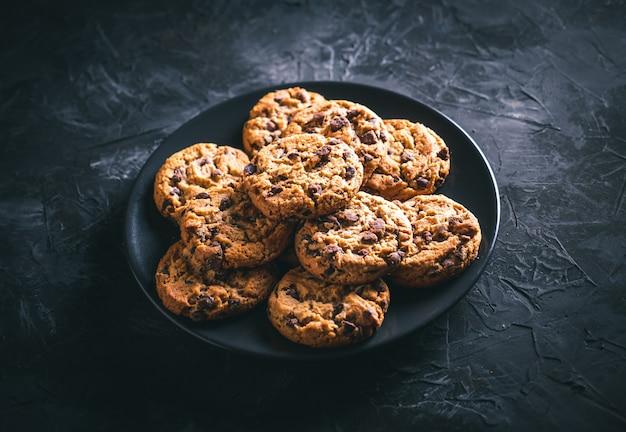 暗いテーブルの上の黒いプレートに自家製チョコレートチップクッキー