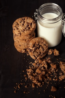 Homemade chocolate chip cookies with bottle of milk and crumbs on rustic wooden table. sweet dessert.