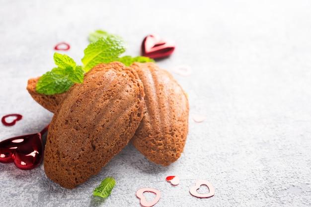 ミントとバレンタインデーの装飾が施された自家製チョコレートクッキーマドレーヌ。テキスト用のコピースペースを備えた休日の食品表面