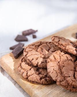 Домашнее шоколадное печенье с шоколадной стружкой на деревянной разделочной доске на светлом столе. макро вид и крупный план