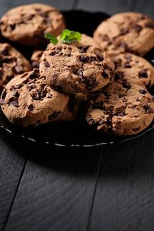 Домашнее шоколадное печенье с листьями мяты на темном деревенском столе
