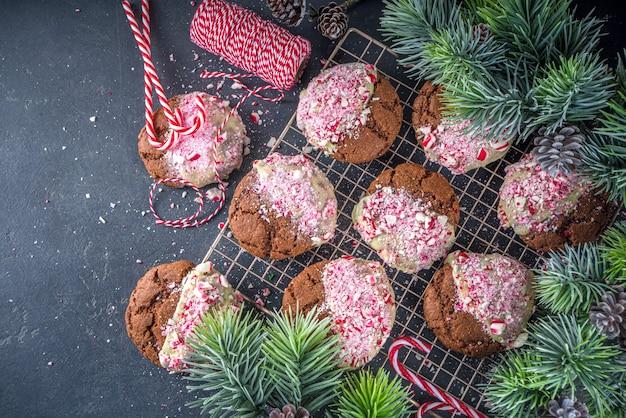 ホワイトチョコレートとキャンディケインのかけらに浸した自家製チョコレートのひびの入ったブラウニークッキー。クリスマスパーティーのおやつ、冬の休日の食べ物のアイデアレシピ