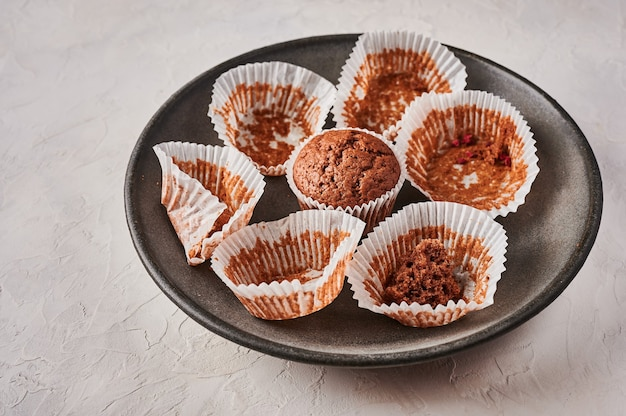나무에 어두운 접시에 빈 포장지 옆에 베이킹 종이 형태로 만든 초콜릿 컵 케이크