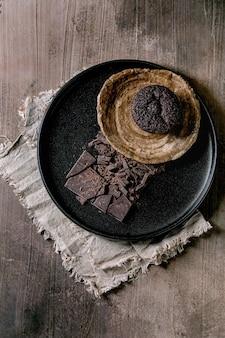 콘크리트 질감 배경 위에 블랙 세라믹 접시에 다진 된 다크 초콜릿으로 만든 초콜릿 컵 케 잌은 머핀. 평면 배치, 복사 공간