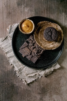 自家製チョコレートカップケーキマフィン、塩キャラメルソースと刻んだダークチョコレートをコンクリートのテクスチャテーブルの上の黒いセラミックプレートに載せたもの。フラットレイ、コピースペース