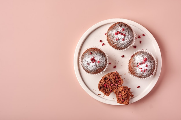 Homemade chocolate cupcakes in baking paper forms and piece of it on light plate on pink powdery