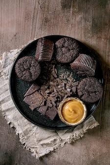 自家製チョコレートカップケーキのマフィンに塩キャラメルソースと刻んだダークチョコレートを、コンクリートのテクスチャテーブルの上の黒いセラミックプレートに載せました。フラットレイ、コピースペース