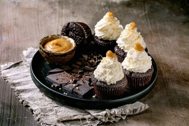 Homemade chocolate cupcakes muffins with white whipped butter cream and salted caramel, served with chopped dark chocolate on black ceramic plate over concrete texture background.