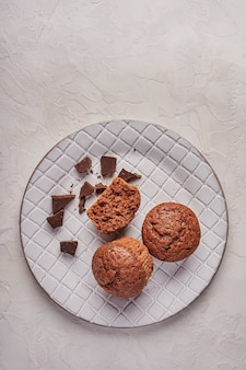 Homemade chocolate cupcakes and pieces of chocolate in textured plate on wooden light background