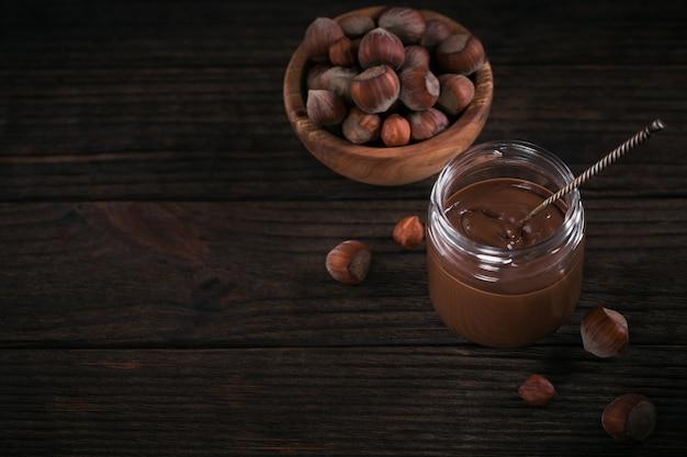Homemade chocolate hazelnut milk spread on glass jar on dark wooden wall