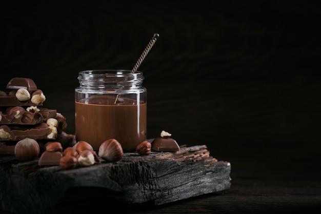 暗い木製のテーブルの上のガラスの瓶に自家製チョコレートヘーゼルナッツミルクスプレッド