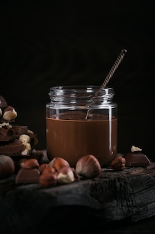 暗い木製の壁のガラスの瓶に自家製チョコレートヘーゼルナッツミルクスプレッド
