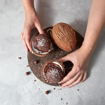 Homemade chocolate ice cream in a coconut shell with whole coconut holding woman's hands on a gray concrete table