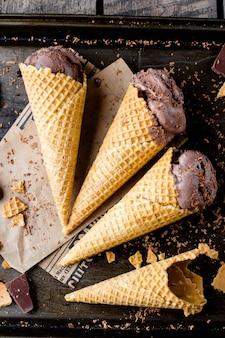 Homemade chocolate ice cream in waffle cones on dark metal background. summer dessert. top view